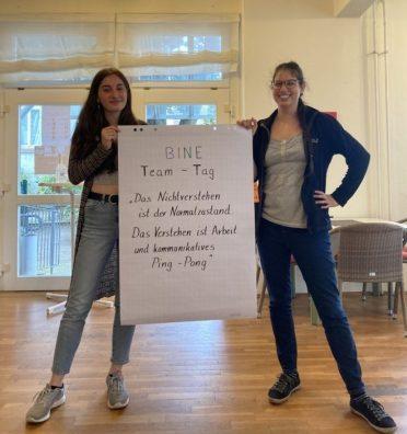 """Rebecca und Judith halten ein Plakat mit der Aufschrift: BINE TEam-Tag. """"Das Nichtverstehen ist der Normalzustand. Das Verstehen ist Arbeit und kommunikatives Ping Pong."""""""
